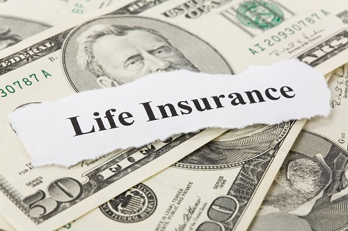 Piece of paper with the words life insurance over a stack of money